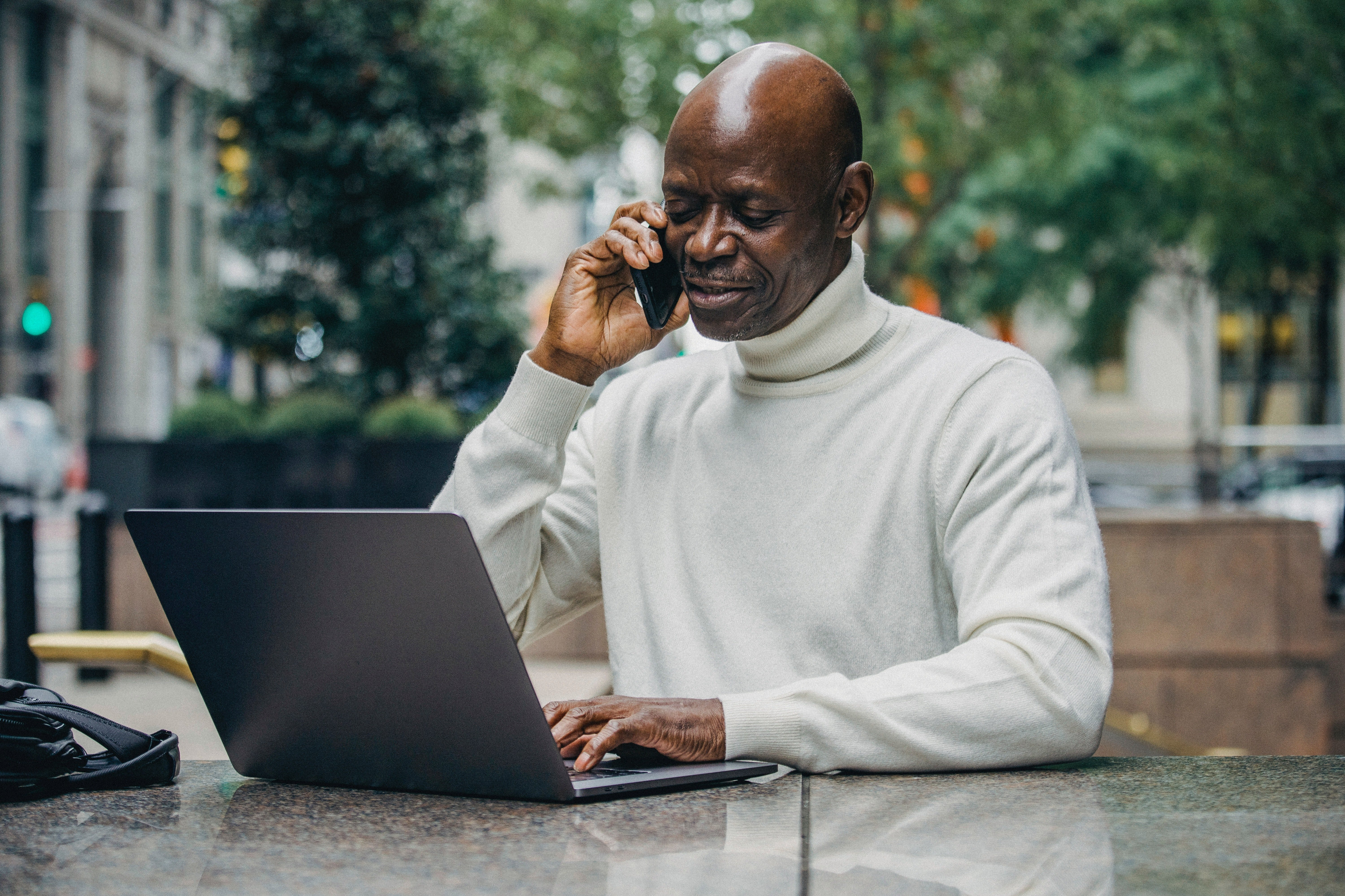 Man talking on phone in front of his laptop   Photo: Pexels