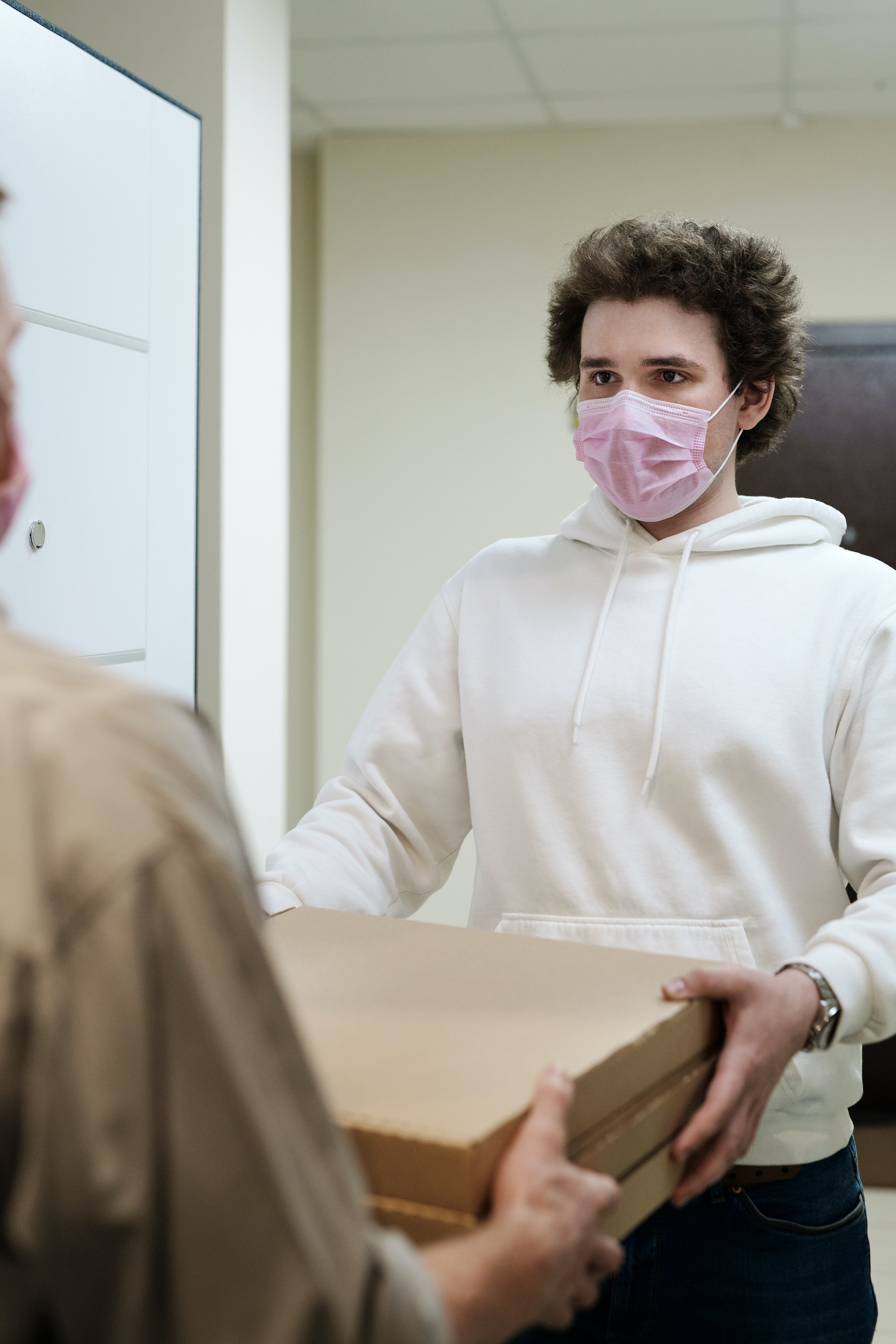 Man in a face mask receiving a pizza delivery | Photo: Pexels