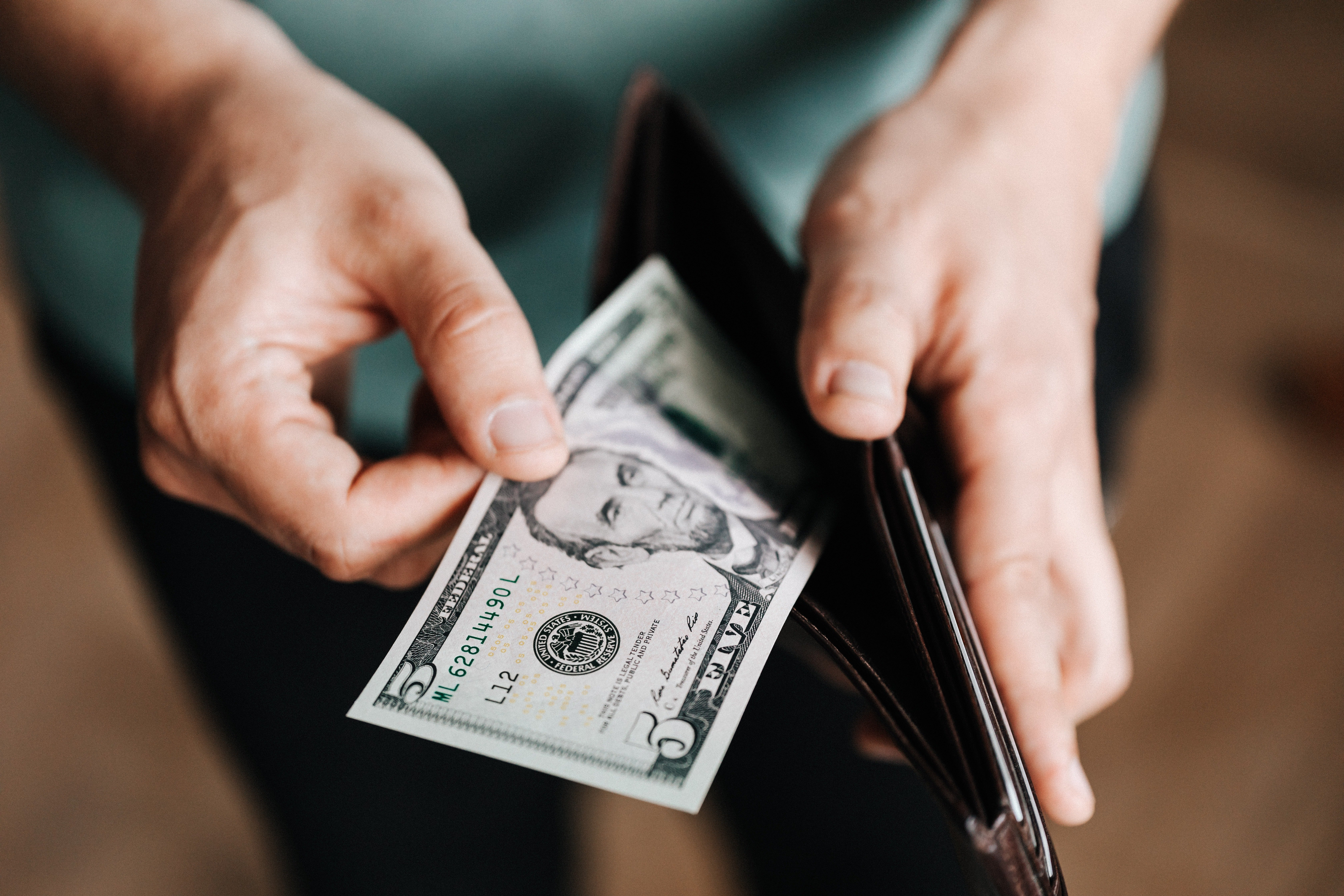 A man taking out money from his wallet. | Photo: Pexels