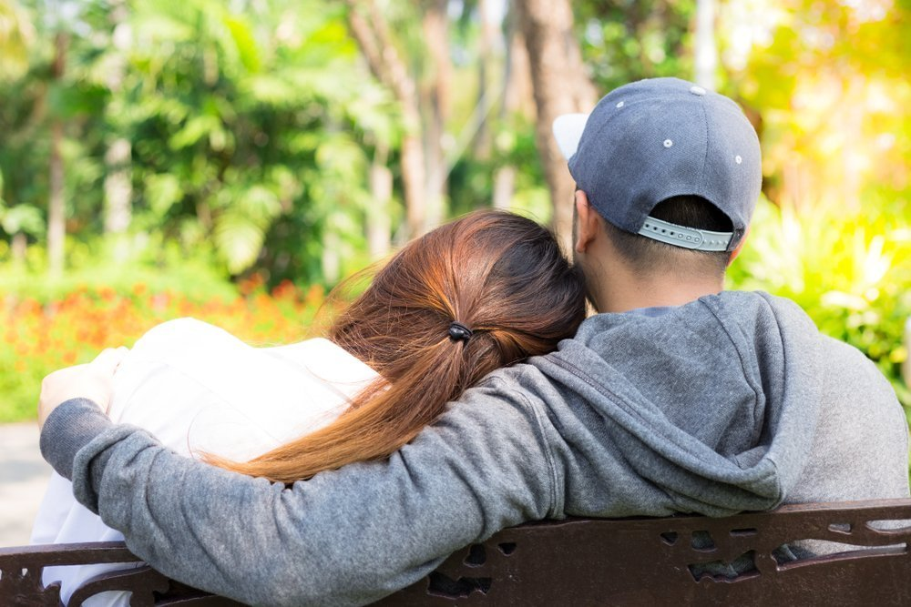 Lovely couple sit in park. Charming beautiful girlfriend lay her head on her boyfriend's shoulder | Photo: Shutterstock