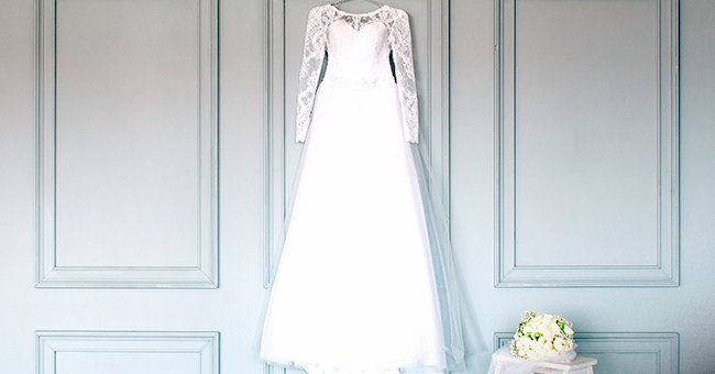 A wedding dress hanging from a wall. | Image: Shutterstock.