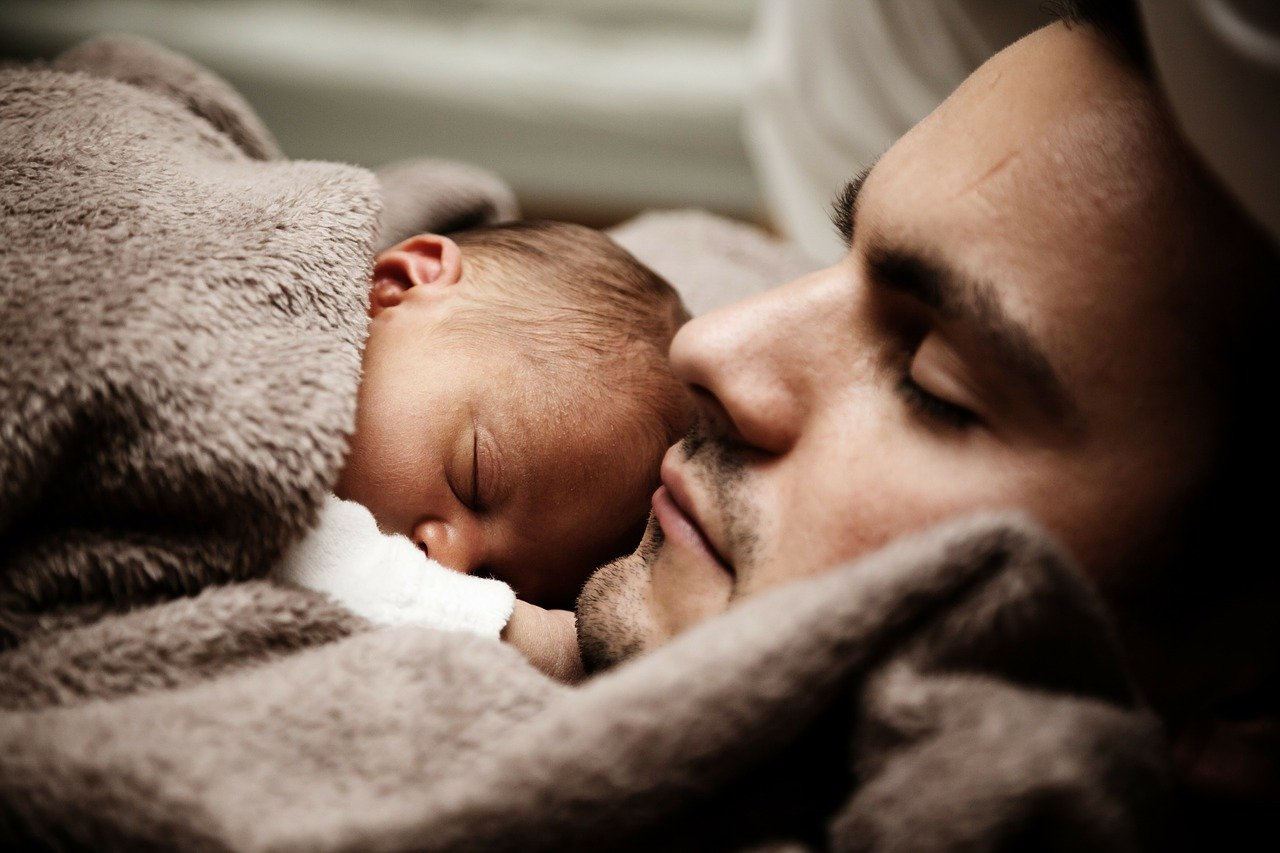 A man sleeping with a baby resting on his chest   Photo: Pixabay/PublicDomainPictures