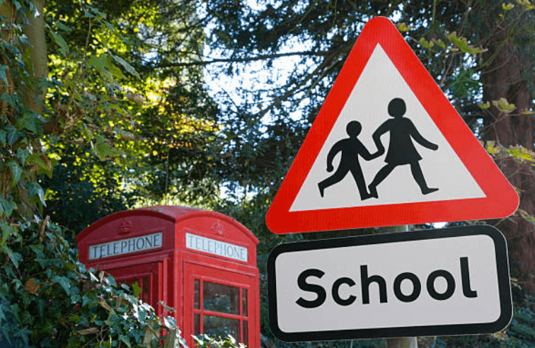 School ahead sign positioned in front of a telephone box, Kent, England | Source: Getty Images