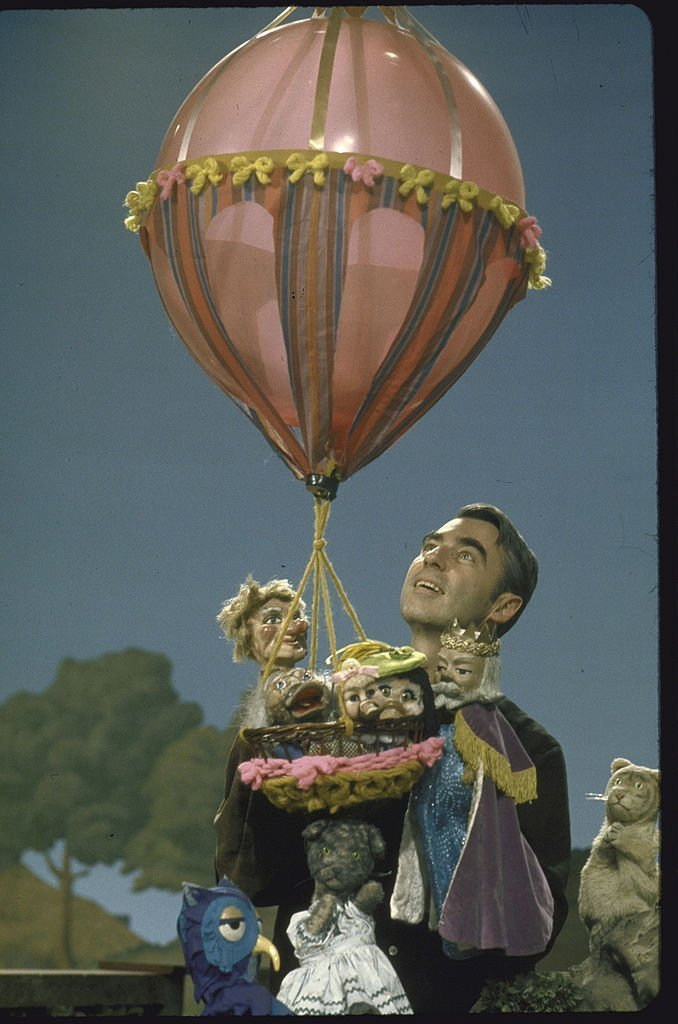 Actor Fred Rogers holding a balloon and puppets in the public TV childrens program Mister Rogers' Neighborhood | Getty Images / Global Images Ukraine