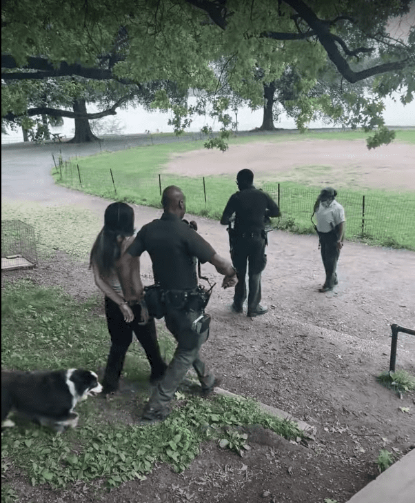 Dora Marchand walks handcuffed by New York park officers. | Source: youtube.com/WestSideRag