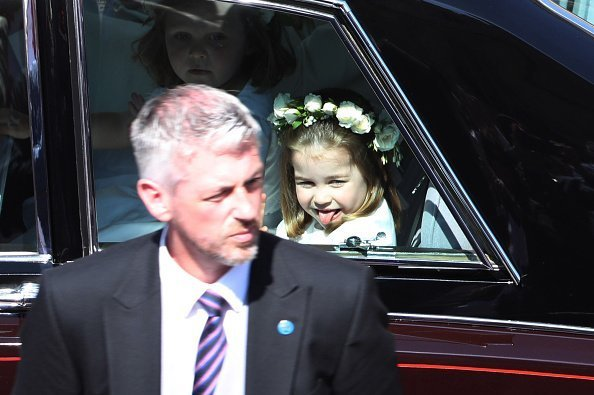 Princess Charlotte waves to the crowd as she rides in a car to the wedding of Prince Harry and Meghan Markle | Image: Getty Images