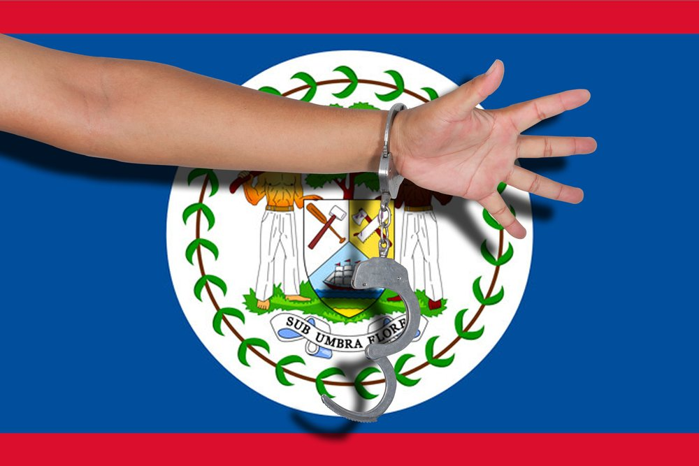 A photo of Handcuffs with hand on Belize flag   Photo: Shutterstock