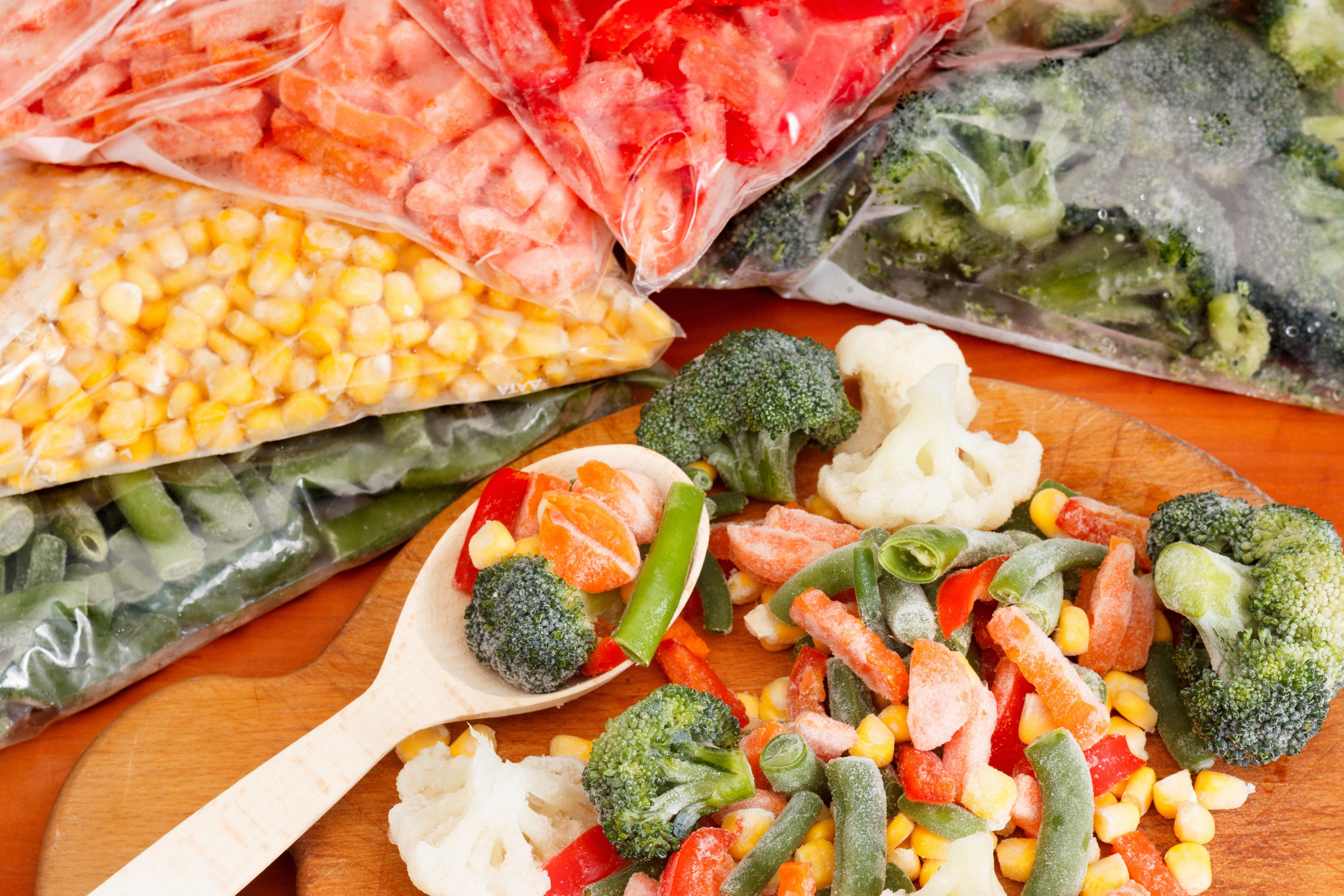Frozen vegetables on cutting board and plastic bags.   Source: Shutterstock