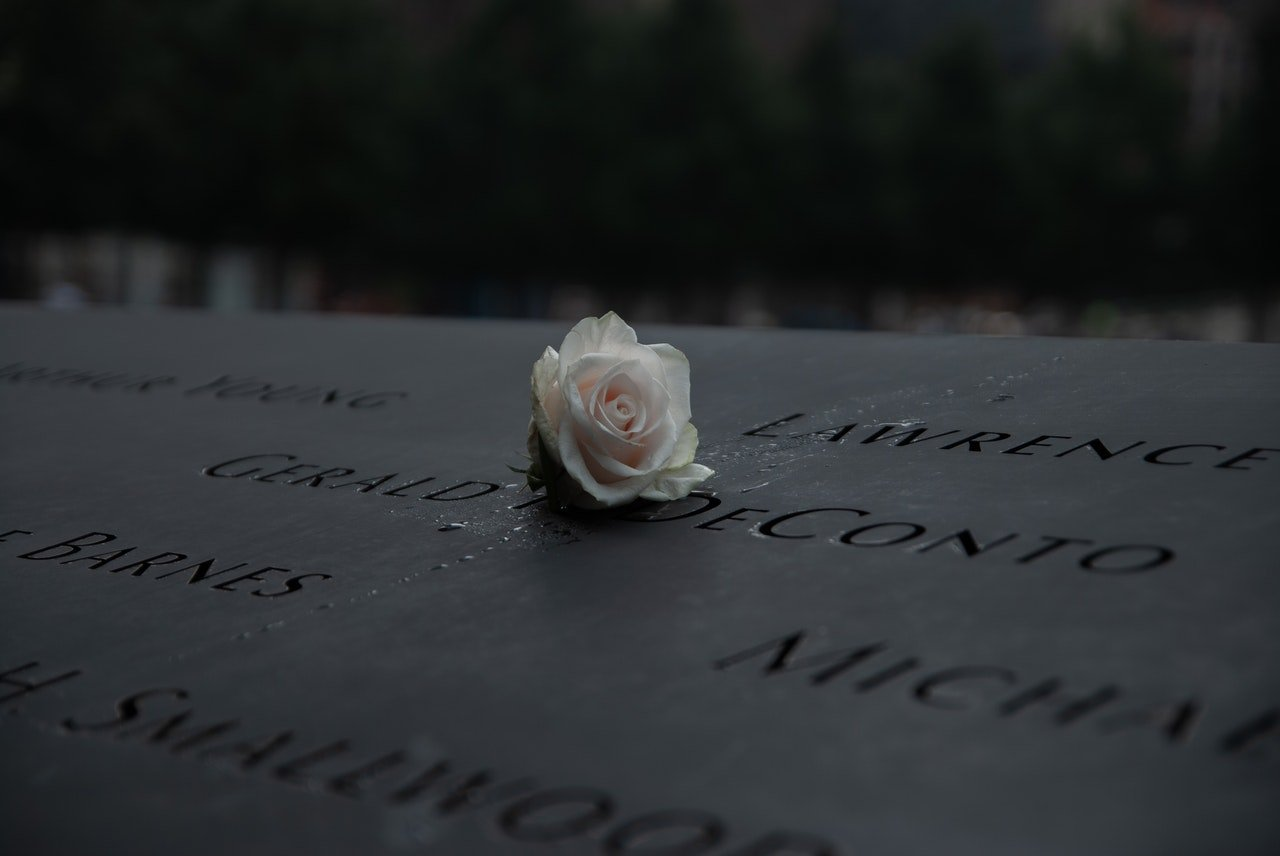 A white rose on a 911 memorilal headstone | Photo: Pexels