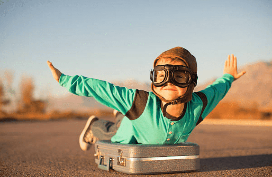 Young boy wearing goggles, lying on suitcase pretends to fly | Source: Getty Images