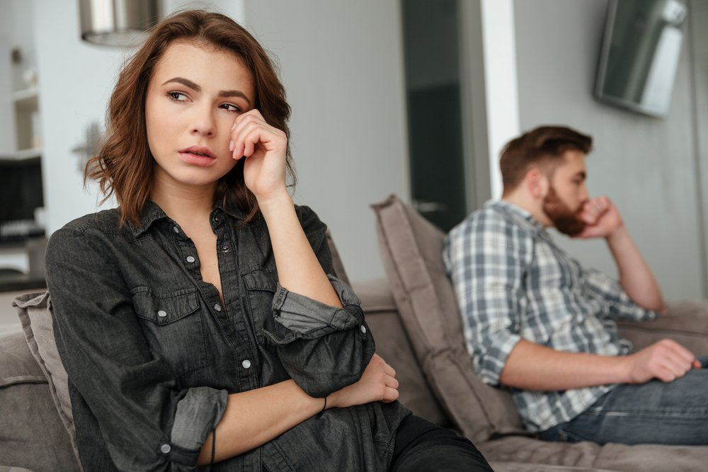 A photo of young sad couple sitting on sofa indoors. | Photo: Shutterstock