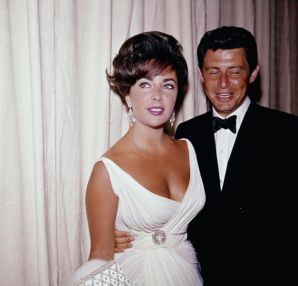 Elizabeth Taylor and Eddie Fisher attending an event, circa 1950-60.  Taylor wears a white dress, with a brooch at the waist.  |  Photo: Getty Images