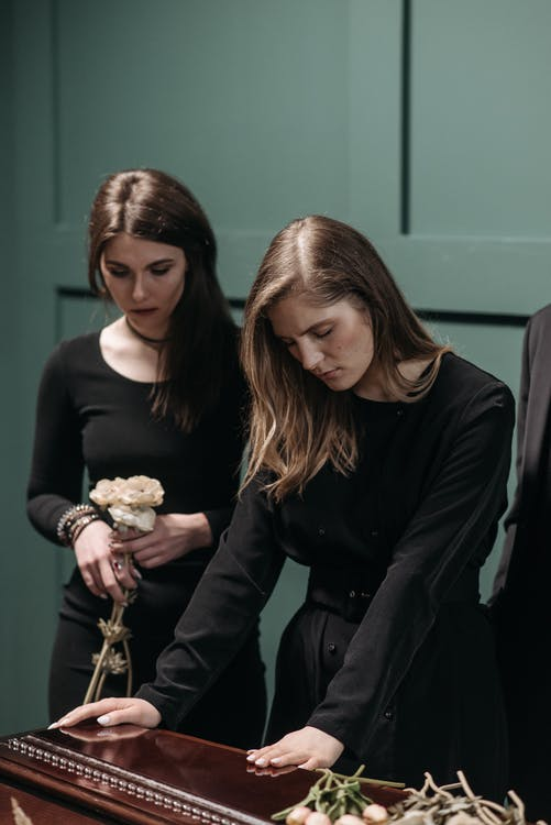 A photo of a grieving woman at a funeral. | Photo: Pexels