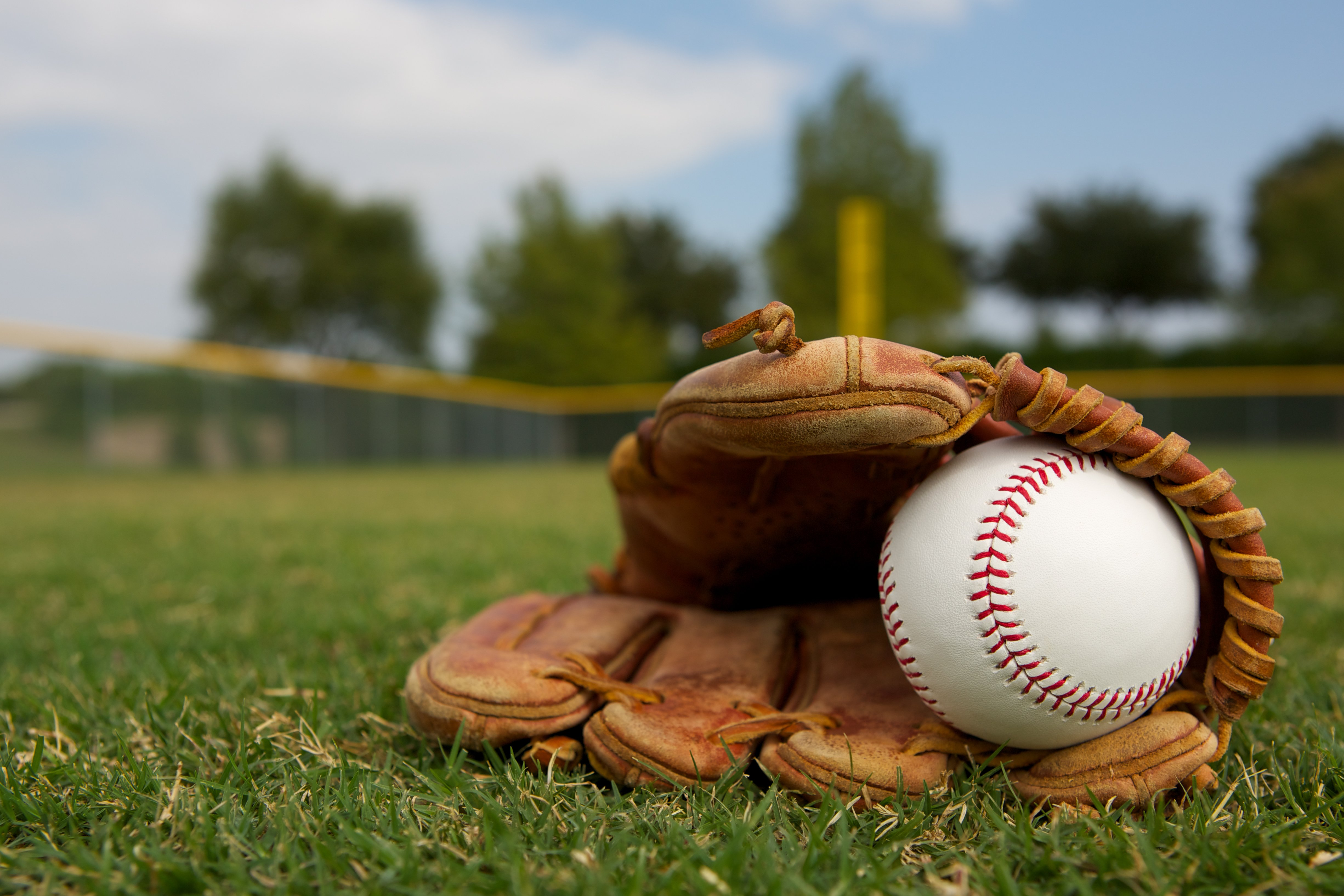 Baseball in a glove in the outfield | Photo: Shutterstock