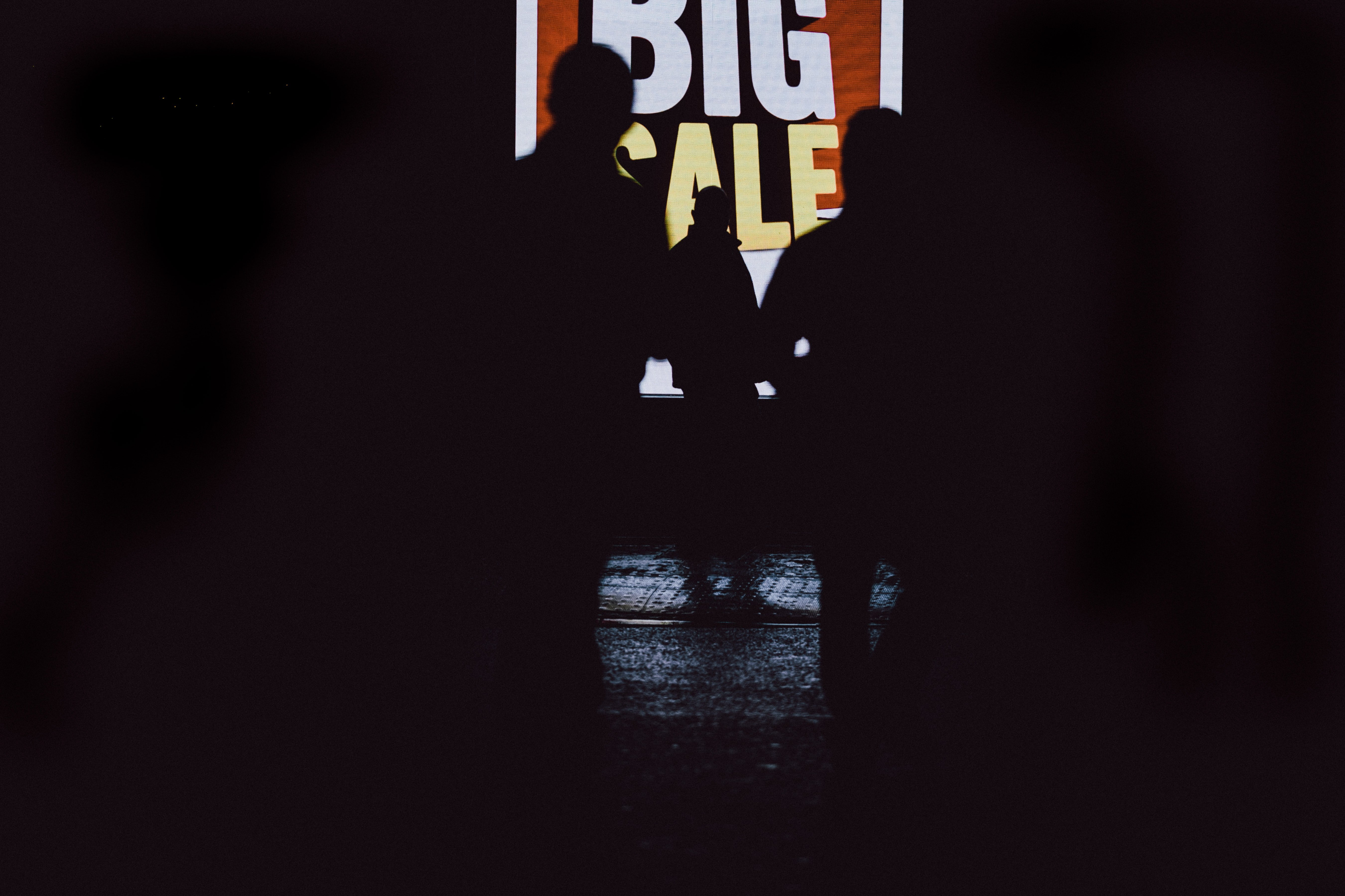 Silhouettes of people in front of a sale sign. | Source: Unsplash