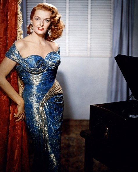Photo of Jane Russell wearing an off-the-shoulder blue and gold dress, with a red theatre curtain behind her, circa 1955 | Photo: Getty Images