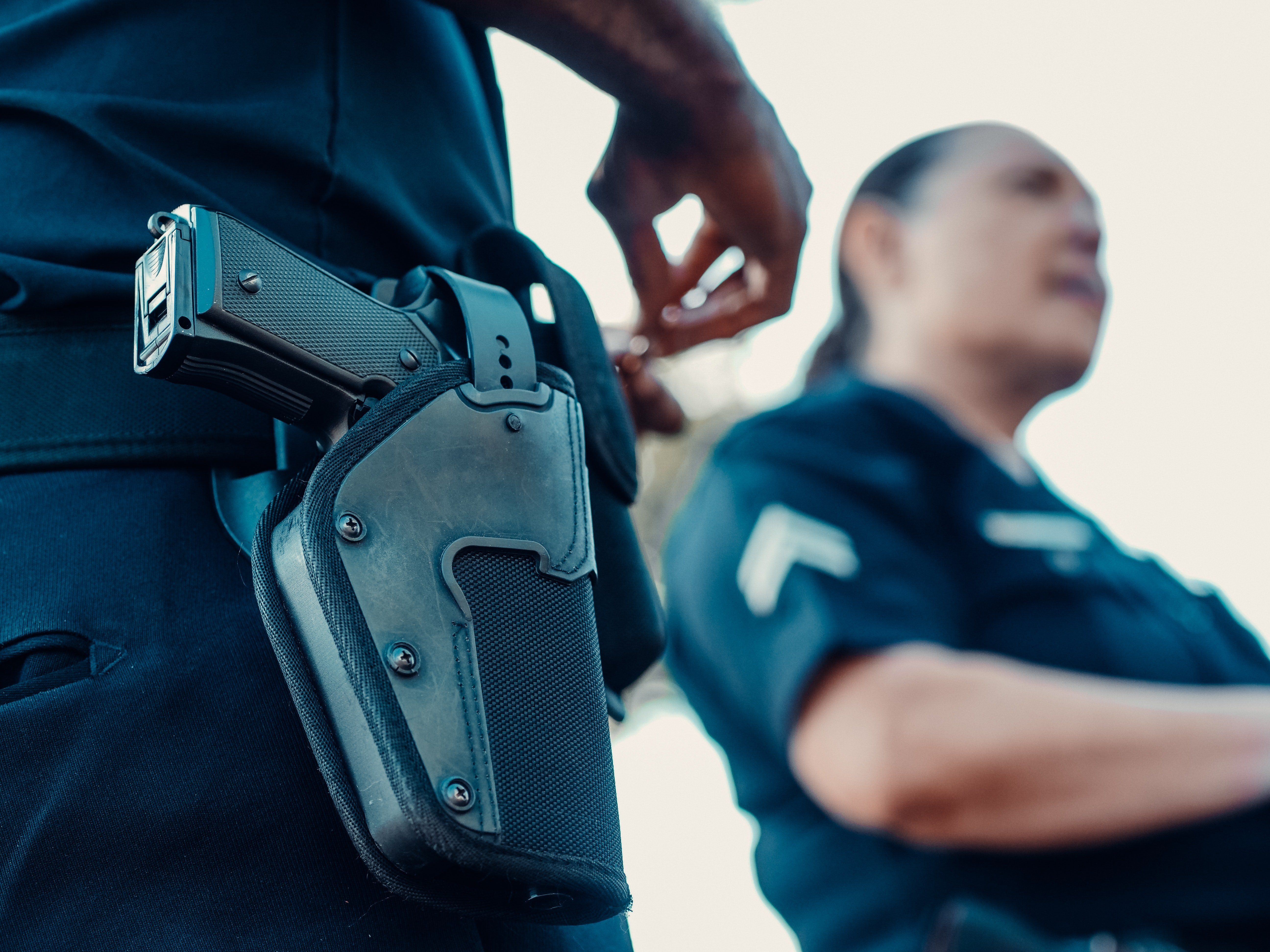 A weapon in the holster with a police women in the backgroung.   Pexels/ Kidel Media