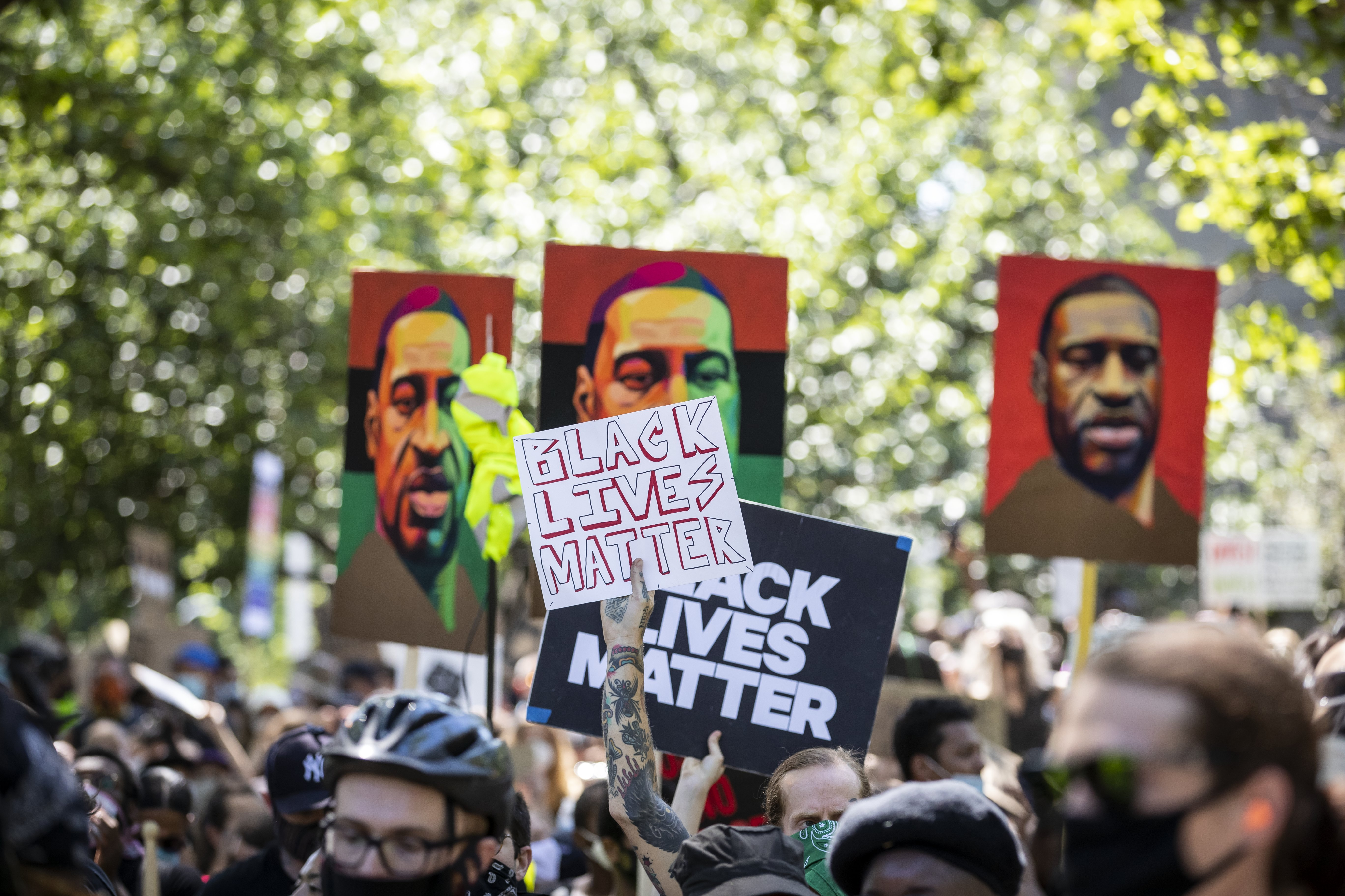 """A protester holds a sign that reads, """"Black Lives Matter"""" with three painted portraits of George Floyd visible behind in Brooklyn Borough, on June 19, 2020 New York   Photo: Getty Images"""