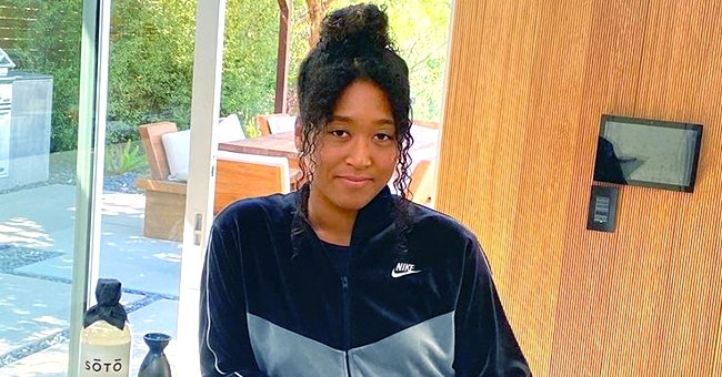Naomi Osaka Sits On a Table as She Models a Louis Vuitton Bag Sporting Ripped Jeans & a Jacket
