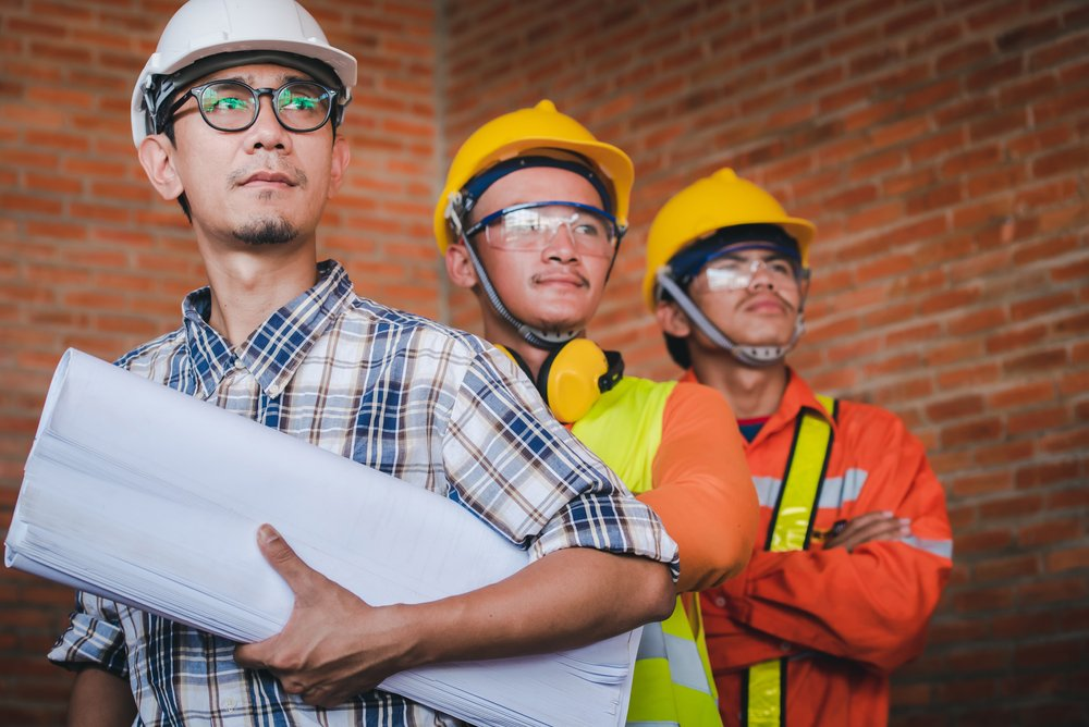 Three male contractors on the way to a site. | Photo: Shutterstock.