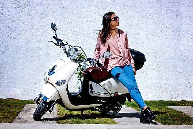 Woman leans on a parked bike | Photo: Pixabay