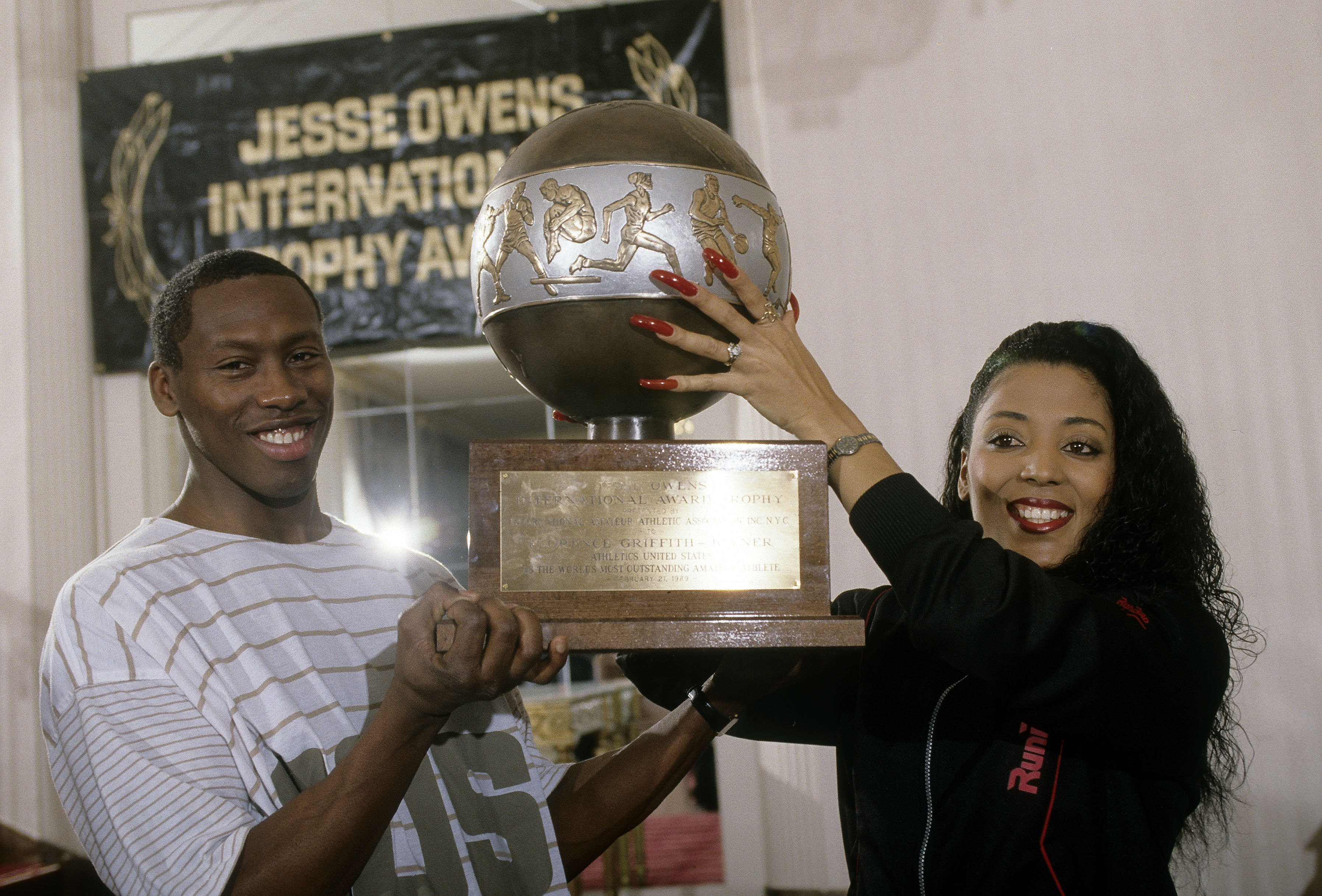 """Florence Griffith Joyner and her husband Al Joyner hold the """"Jesse Owens International Awards Trophy"""" presented to her on February 21, 1989 
