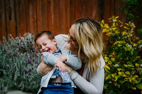 A woman playing with a young boy as she tickles him   Source: Unsplash