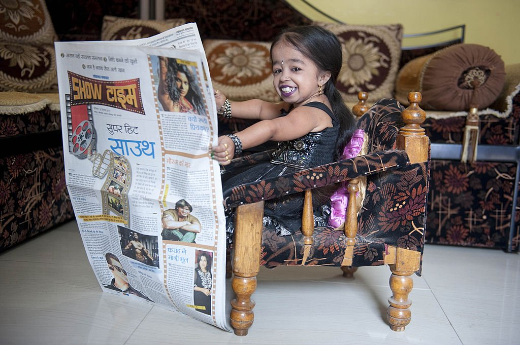 Jyoti Amge photographed reading a newspaper in Nagpur, India on December 10, 2011. | Photo: Getty Images