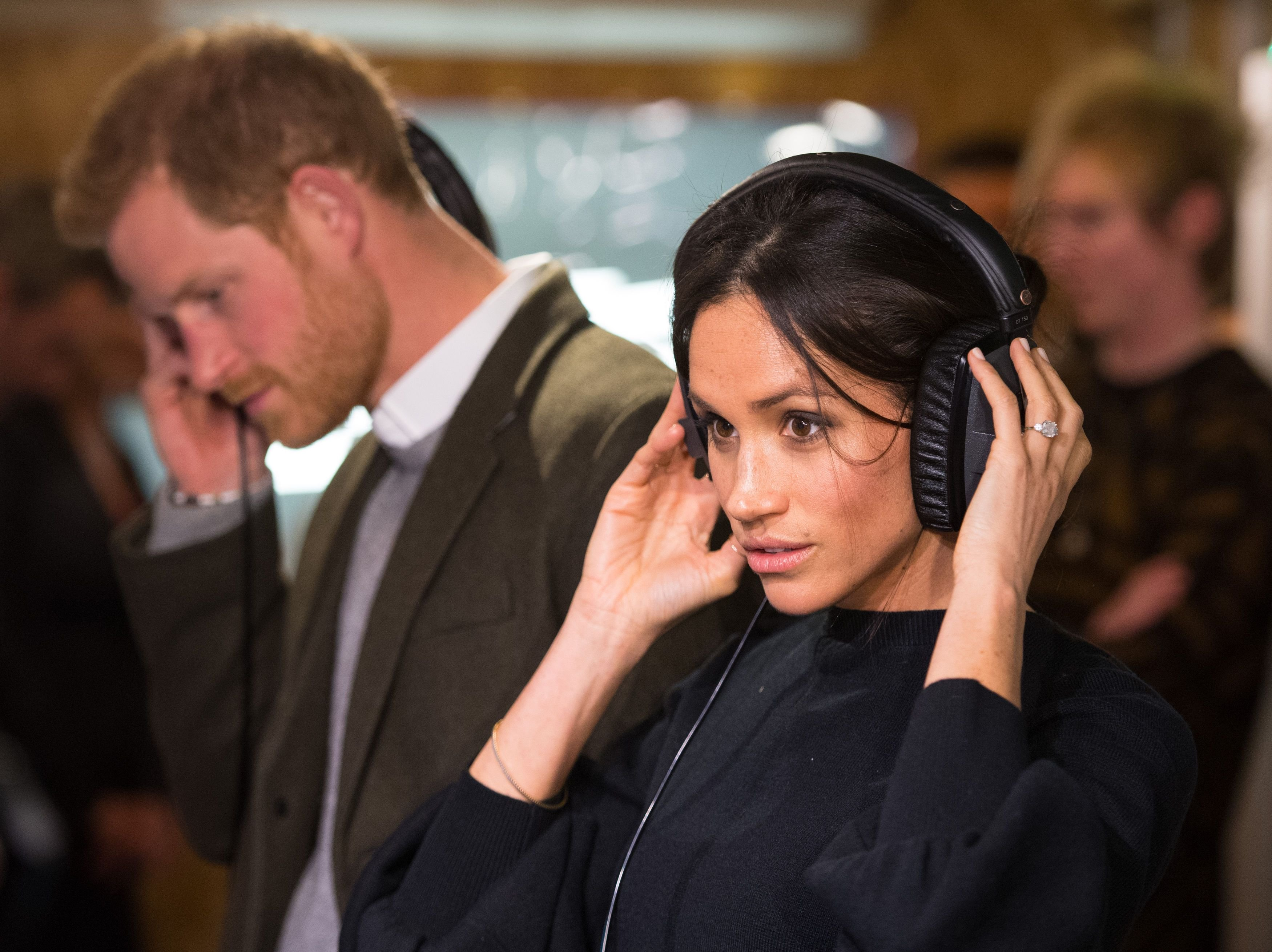 Prince Harry and Meghan Markle listen to a broadcast at Reprezent 107.3FM in Pop Brixton on January 9, 2018