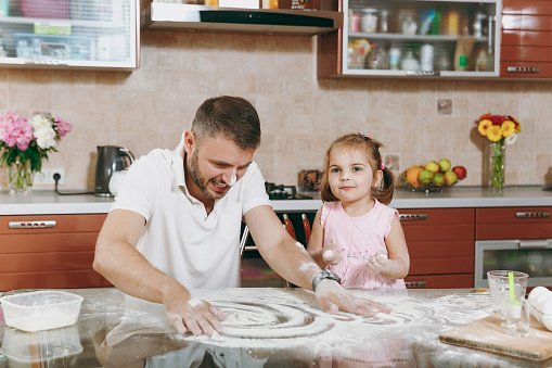 Photo of little kid and her dad drawing on scattered flour on kitchen table | Photo: Getty Images