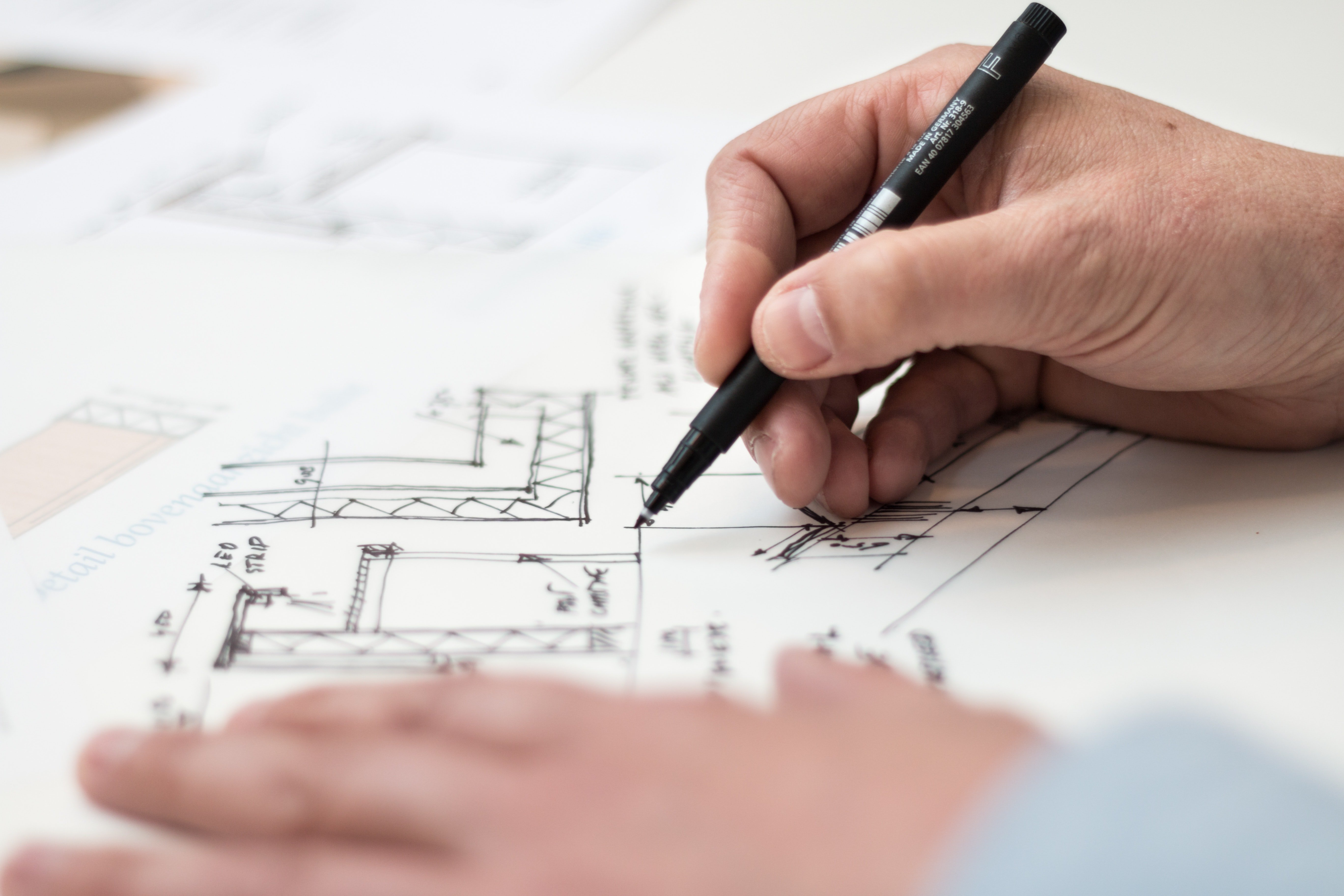 Pictured - An individual with a black pen designing a structure   Source: Pexels