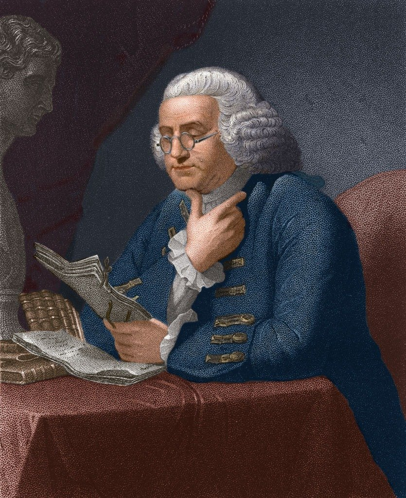 Illustration of American statesman and scientist Benjamin Franklin (1706 - 1790) as he reads at a table, late 18th century.   Photo: Getty Images