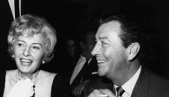 American film stars Barbara Stanwyck and Robert Taylor who were married in 1939 and divorced in 1951 at a press party to mark the start of production of their new film 'The Night Walker'. May 1964. | Source: Getty Images