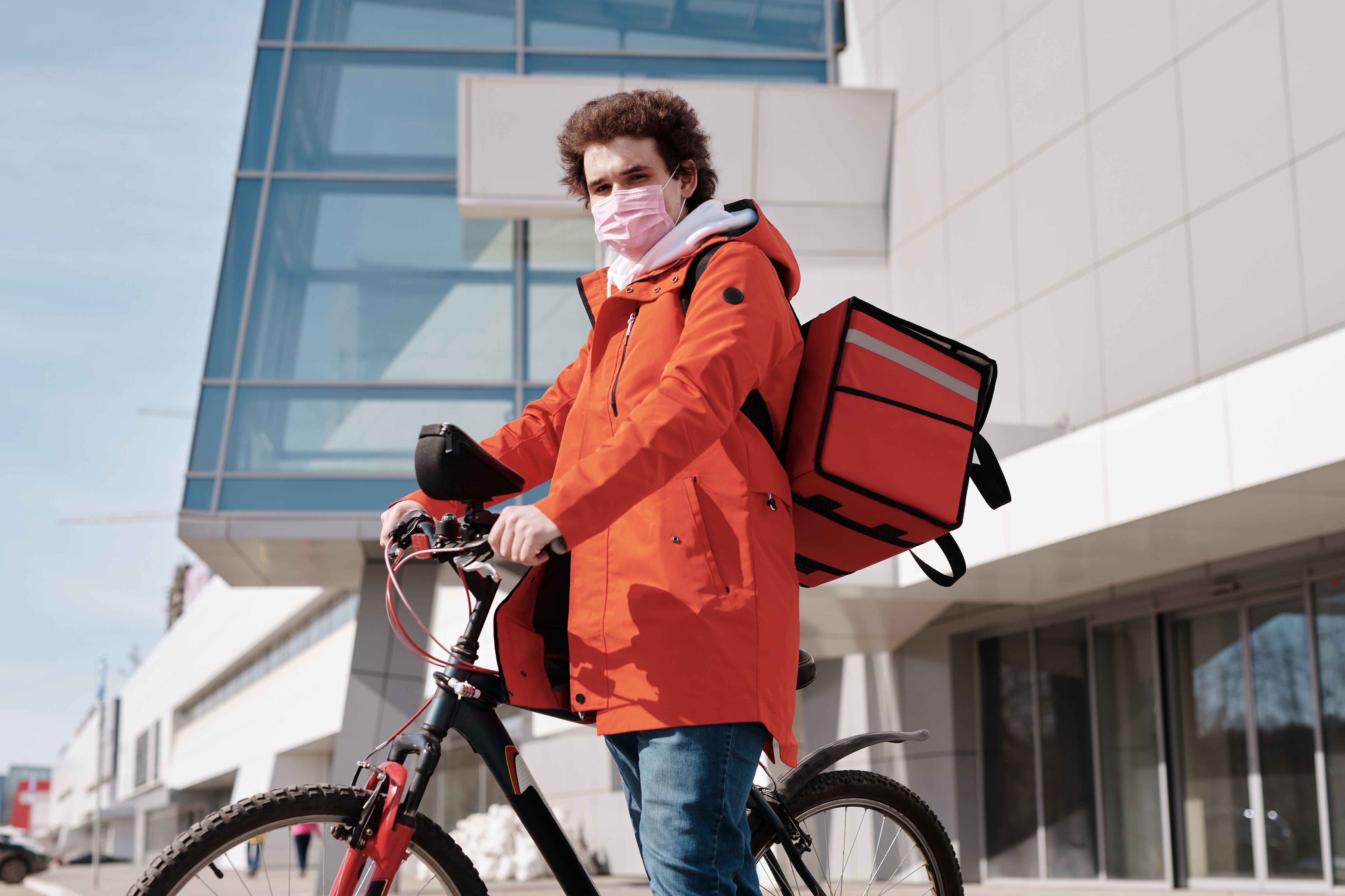 Delivery man wearing a face mask and riding a bicycle   Source: Pexels