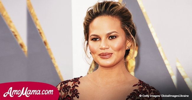 Chrissy Teigen rocks a vibrant floral outfit, revealing her glow throughout her pregnancy