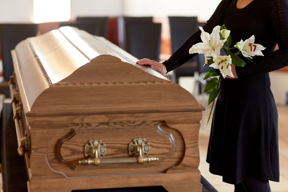 A woman with white lily flowers and hands on a coffin at funeral.   Photo: Shutterstock.