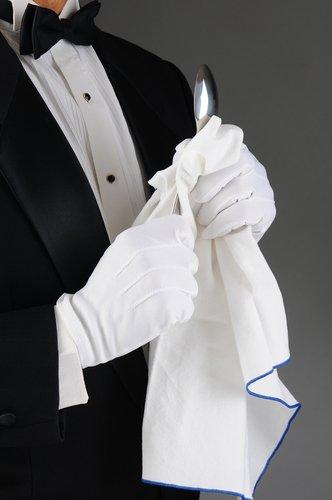 A waiter polishing a spoon. | Source: Shutterstock.