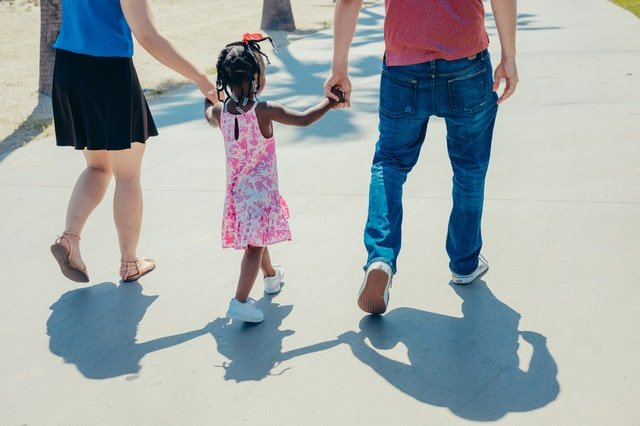 couple holding little girl's hand | Source: Pexels