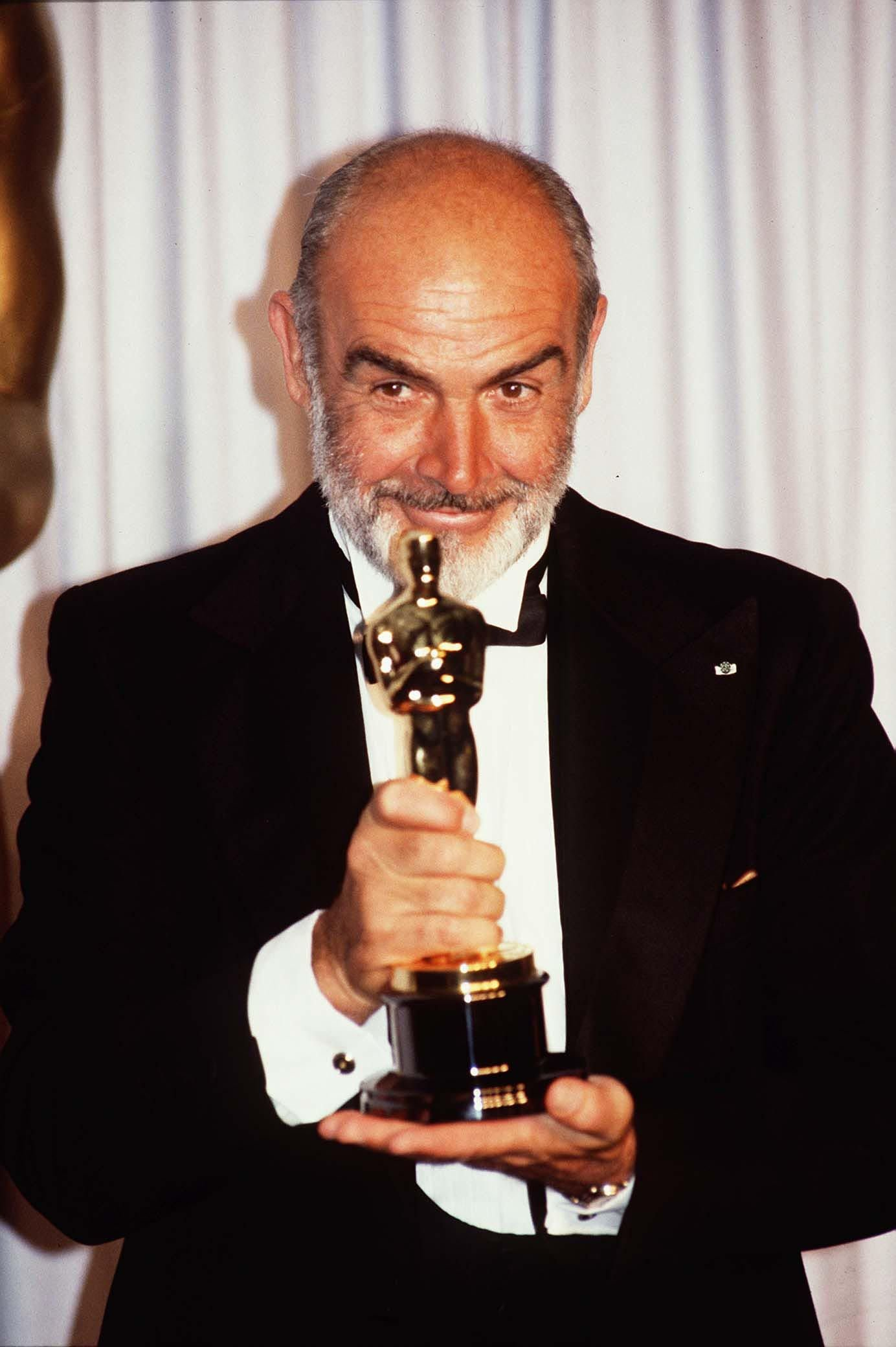 Scottish Actor Sean Connery holding an Academy Award for Best Actor in a Supporting Role iduring the 1988 Oscars Ceremony | Photo: Photoshot/Getty Images