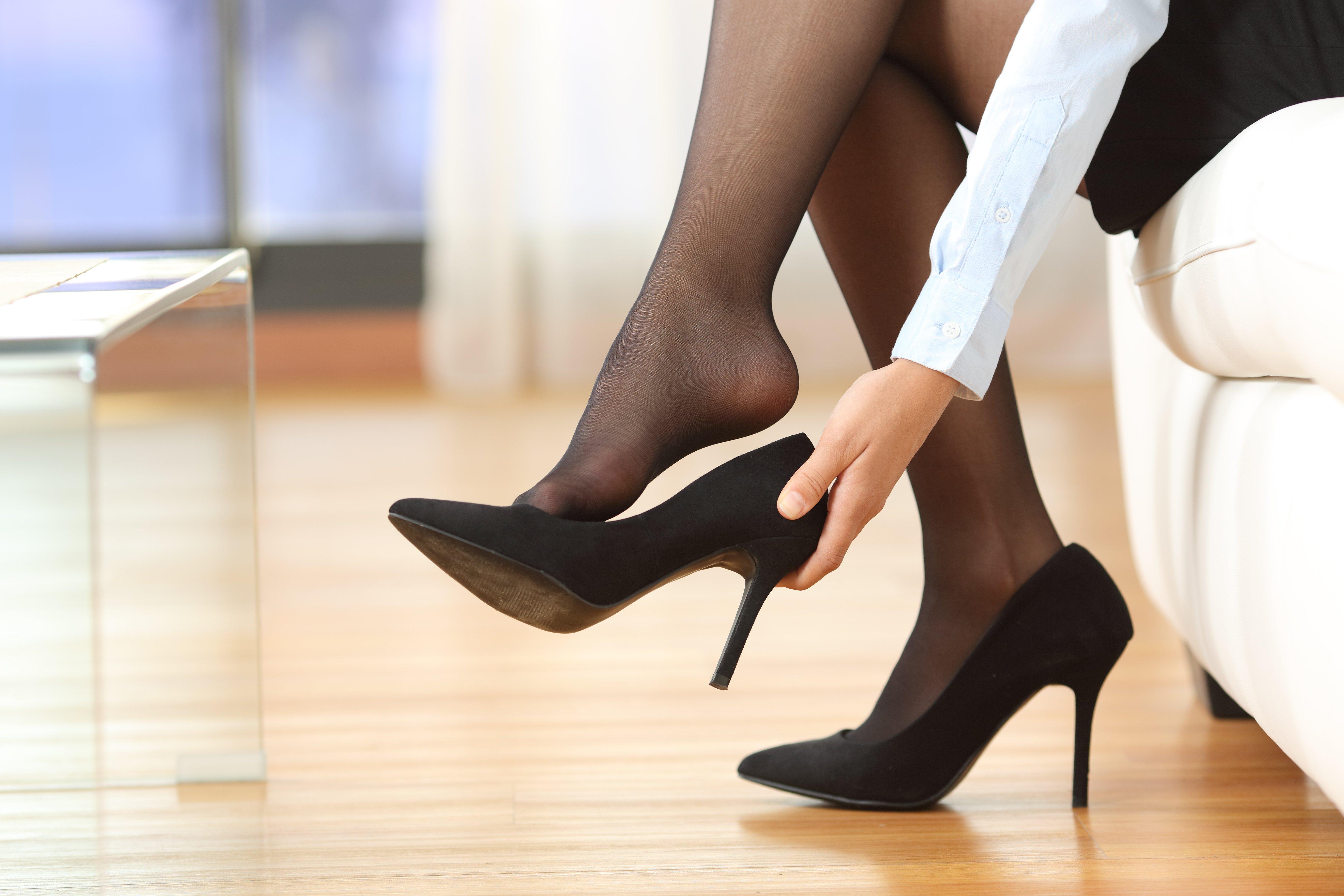 Empresaria quitándose los zapatos de tacones altos después del trabajo. Fuente: Shutterstock