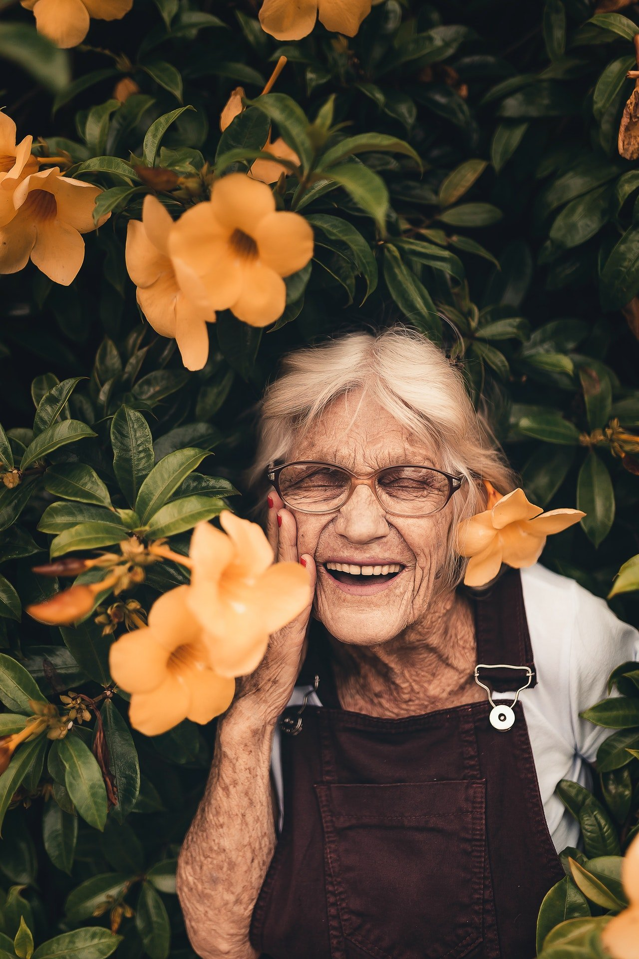 Photo of a woman smiling in the garden | Photo: Pexels