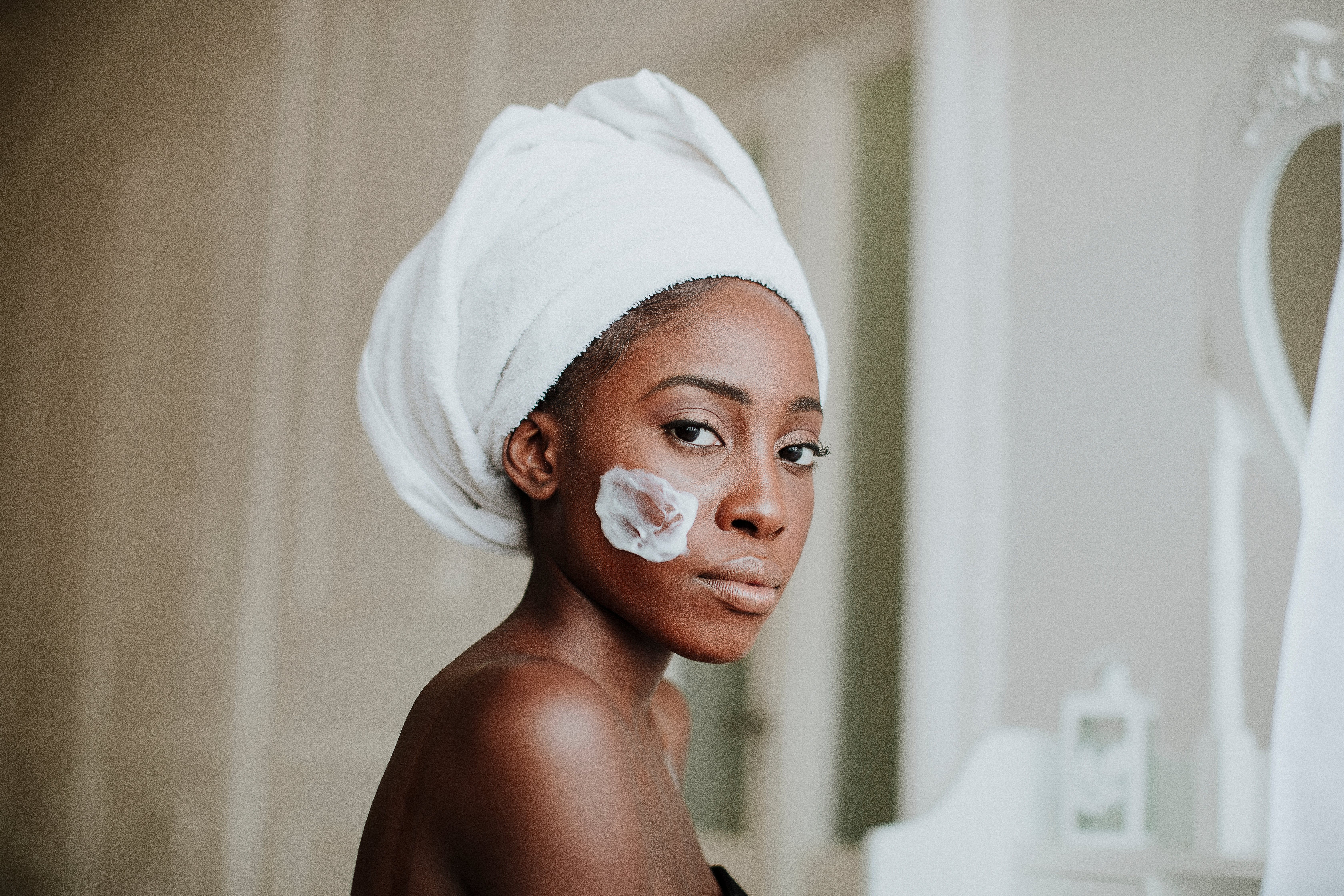 Portrait of beautiful young Afro-American woman taking care of her skin | Photo; Shutterstock