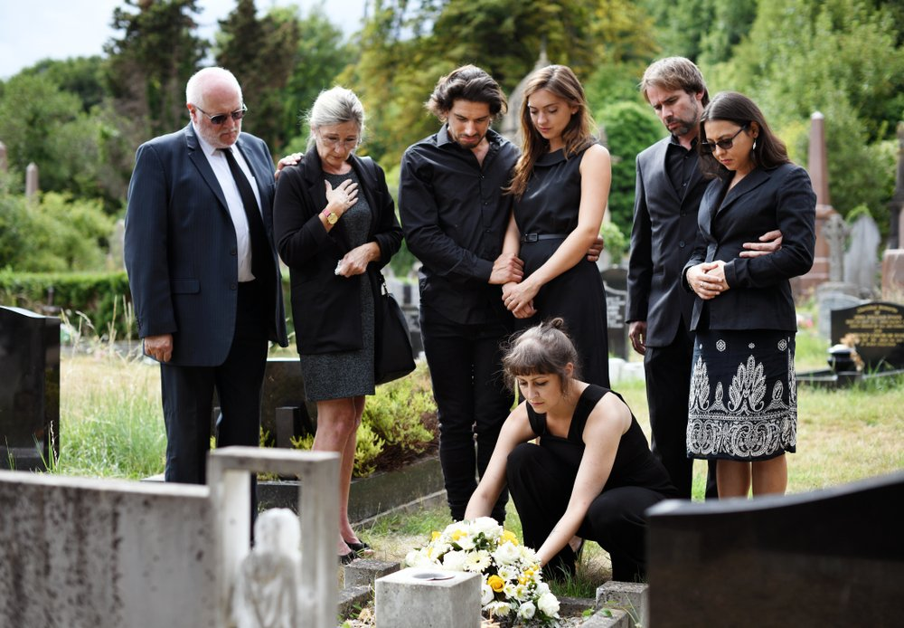 A grieving family laying flowers on the grave.   Photo: Shutterstock.