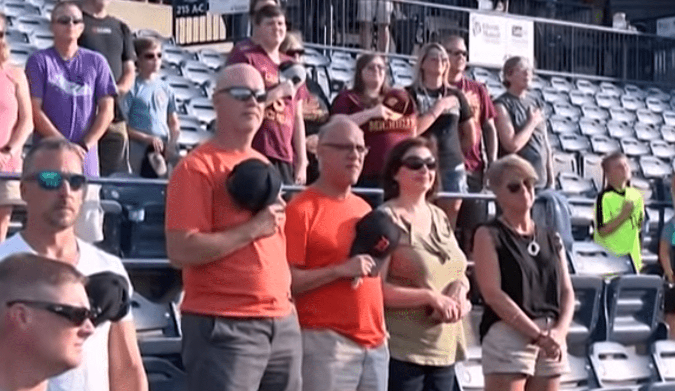 Spectators at a baseball game watch in awe as an elderly veteran sings the national anthem | Photo: Facebook/wmwcaps