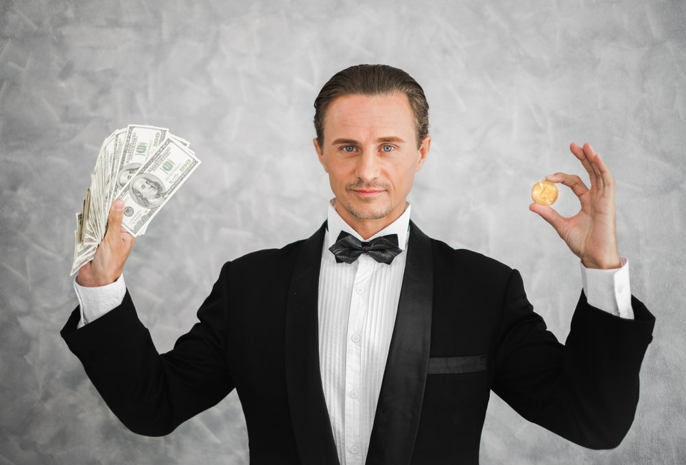 A millionaire holding bitcoin and dollar money. | Photo: Shutterstock