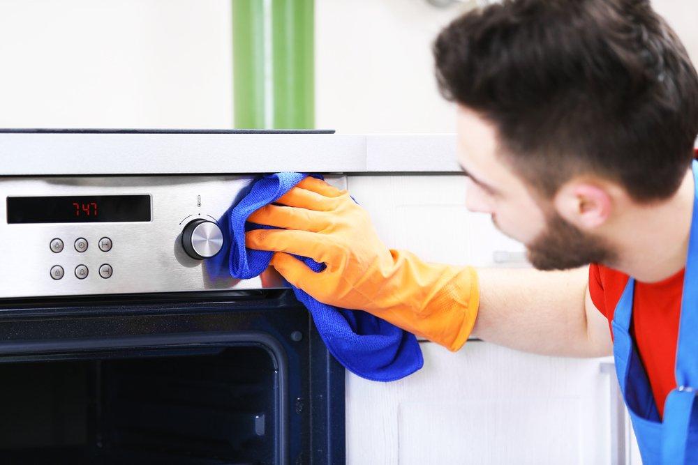 Persona limpiando el horno de la cocina-Imagen tomada de Shutterstock