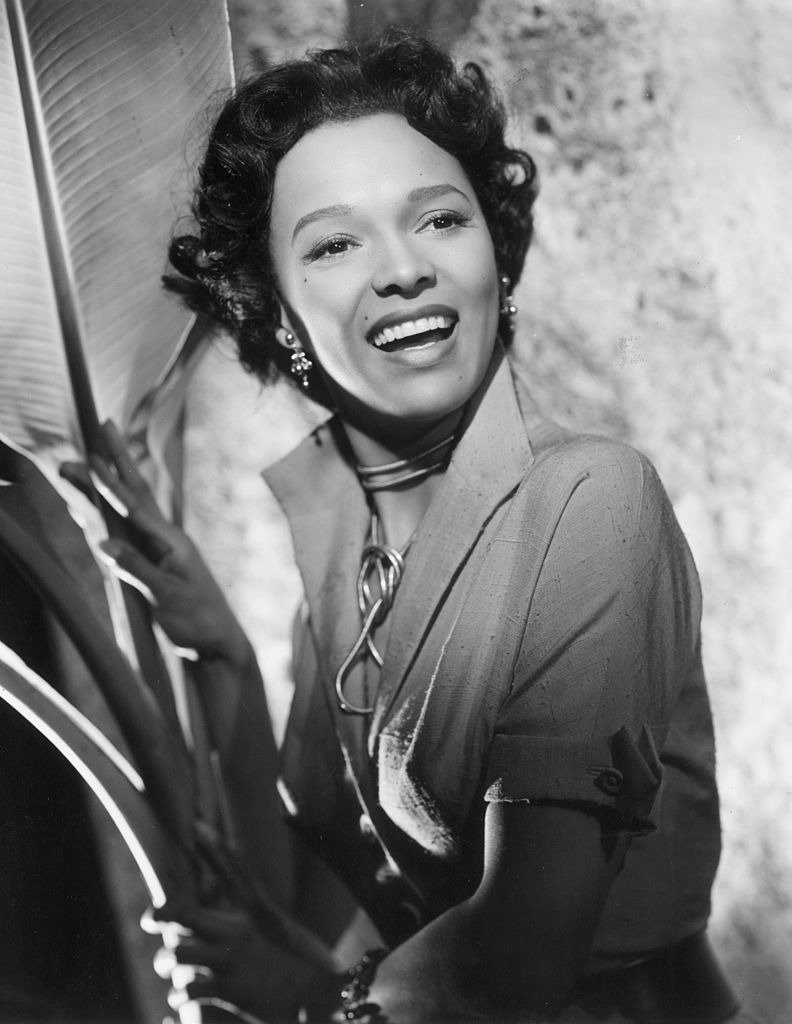 Dorothy Dandridge smiles as she stands next to a large palm frond in a promotional portrait for director Robert Rossen's film, 'Island in the Sun'   Photo: Getty Images