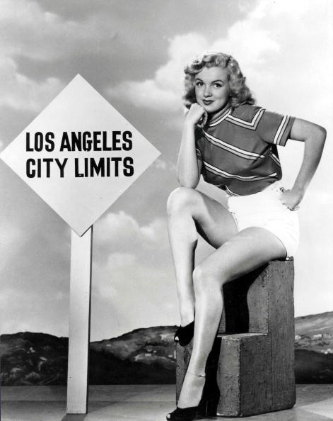 "Marilyn Monroe poses in front of a signpost reading ""Los Angeles City Limits"" wearing t-shirt and shorts, circa 1950s. 