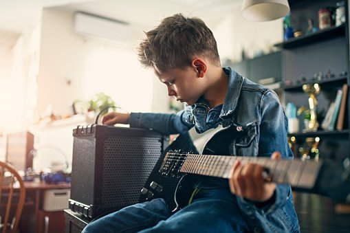 Photo of a little boy playing electric guitar in the living room | Photo: Getty Images