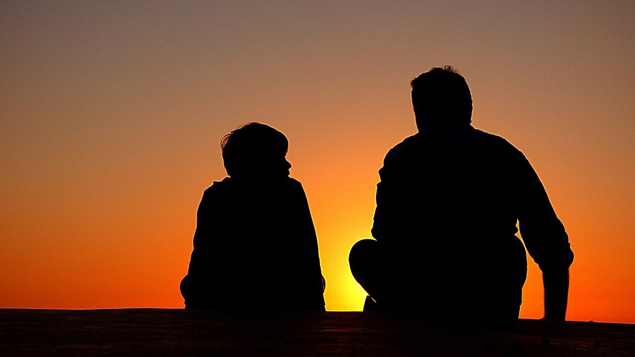 A picture of a father and his son sitting and talking while watching the sunset. | Photo: Pixabay